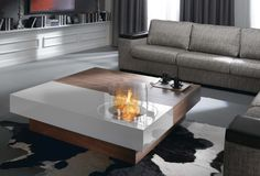 This fire pit coffee table is hand produced with walnut veneer and works exclusively with ethanol (no electricity or connections). The colored area sports a high-gloss varnish and the fire pit burns within a stainless steel plate. The ethanol reservoir contains half a liter (0.5) and burns for up to 1.5 hours. Fuel refilling is achieved by simply picking the burner up from the table top.