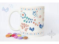 Hrnček s motívom inšpirovaným folklórnymi ornamentmi. Príjemné pastelové farby navodia upokojujúcu atmosféru pri pití Vášho obľúbeného teplého nápoja.