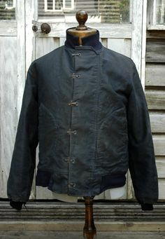 Waxed canvas jacket with hook and eye closure.  Not quite hook and eye, the fittings on the right side are hinged and snap shut.  I used to have a pair of rubber boots with these fittings as a kid in the 1970s.  Note the pockets, huge, rounded and side entry for your hands or a pair of gloves.