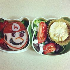 Super Mario bento. Open faced turkey sandwich with craisin and fruit leather embellishments. Strawberries, salad and corn on the cob.