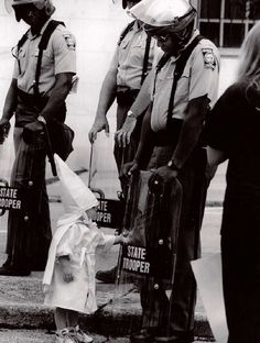 photo by Todd Robertson  Georgia State Trooper in riot gear at a KKK protest in a north Georgia city back in the 80s.  The Trooper is black. Standing in front of him and touching his shield is a curious little boy dressed in a Klan hood and robe.