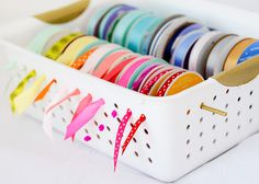 """My ribbon holder saves me from digging when I'm sewing. Slide spools onto a 14 1/2 inch thin wooden dowel, fit the stick across a slotted plastic bin's top row of holes, and pull ribbon ends through the sides. Repeat with as many rolls as your bin can hold."" –Halsey Bishop of Spunky Junky  - GoodHousekeeping.com"