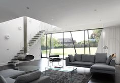 Living room with floor-to-ceiling windows and a suspended fireplace hanging from the second floor.