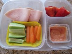 Roast turkey slices, cucumbers and lightly steamed carrots, and sliced strawberries.
