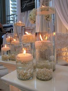 Glass cylinders filled with water and floating candles and pearls. Decoração casamento