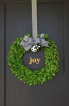 Black, gold and white holiday decor! We used a boxwood wreath, black & white striped ribbon and DIY black & white polka ornaments. We added a custom gold Joy decal to finish off the look. By jane can...