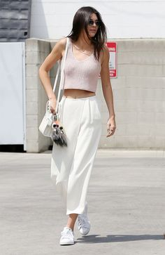 Kendall Jenner wears a crochet v-neck crop top with white wide-leg pants, white crossbody bag and white tennis shoes.