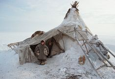 A young Tundra Nenets girl holds two puppies at a camp on the Gydan Peninsula. Western Siberia, Russia.