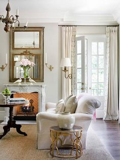 Light layers should be placed to bounce illumination throughout a room and eliminate shadows from corners. In this living room, a burnished metal chandelier supplies overall light and visual interest. Twin sconces supply soft accent lighting and define the area around the fireplace and mirror. A scrolling floor lamp offers task lighting for the seating area.