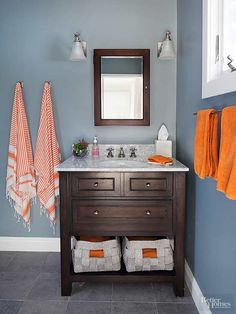 Kick up calming blues with spots of energetic orange. Blue-gray wall color tempers the brightness of orange linens and accessories. A rich brown vanity with matching mirror frame heat things up./