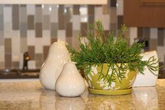 Choose green in pottery and plants as the accent to this neutral kitchen display.