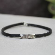 A narrow bar features an inspirational word on a thin leather bracelet. Wear this bracelet daily to remind you of how much you are loved. Measurement: Fits up to wrist Materials: Silver with black: white bronze and leather Love Bracelets, Black White, Bronze, Inspirational, Bar, Silver, Leather, How To Wear