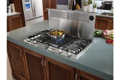 Pop-up ventilation for gas stoves in kitchen islands. Tucks under counter when not in use.