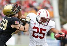 Stanford running back Tyler Gaffney (25) holds off Army linebacker Thomas Holloway (29) during the second half. Gaffney was penalized for face masking. Stanford won, 34-20. (Mike Groll/AP)