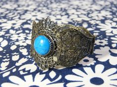 Filigree metal and faux turquoise stone cuff bracelet - boho Arabian style - French 80s vintage to be worn up your forearm, Scheherazade style made of filigree metal & a faux turquoise stone (plastic) the bracelet is a bit out of shape, light traces of use on the faux turquoise stone good condition  diameter circa 6 cm (= 2.4 inches) maximum width circa 4,5 cm (= 1.6 inches)   PLEASE READ MY POLICIES PAGE BEFORE ORDERING!  www.facebook.com/labaronnevintage www.pinterest.com/baronnevintage