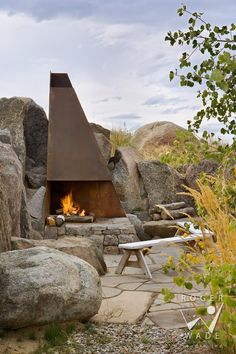 outdoor steel fireplace built into the rocks.