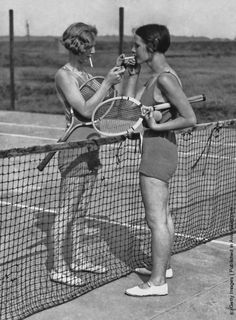 Two women lighting cigarettes on a tennis court in Essex, England circa 1930's. (Photo by Keystone View/FPG/Getty Images)
