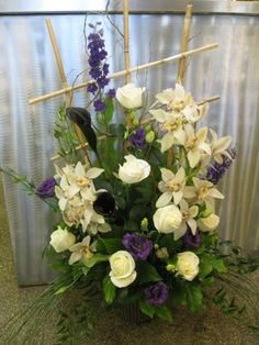Contemporary arrangement - one-sided is great for a registration or cake table where your guests won't view the arrangement from all sides! Bamboo lattice, cymbidium orchids, roses, lisianthus and calla lilies
