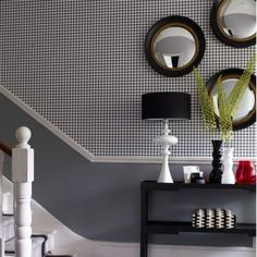 Classic-monochrome-entrance-hall-with-geometric-wallpaper-and-porthole-mirrors