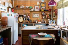 Casa pequena, casa charmosa, cozinha com revestimento em madeira, plantário e muitos detalhes.