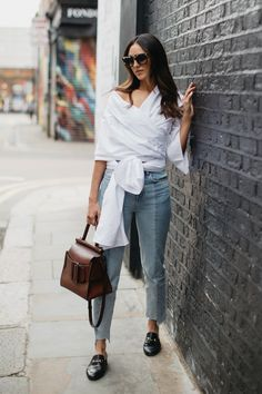 If you're in the market for a new It bag this season, we highly recommend the Karl Bag from Boyy. It's a classic top-handle bag with a whimsical twist thanks to an oversized buckle. We absolutely adore how Soraya styled hers with a white wrap top, deconstructed raw-hem jeans, and Gucci mule flats.