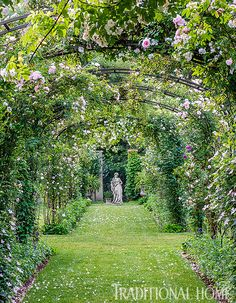 'New Dawn', 'White Dawn', and heritage roses climb the arbors running on the cross axis in a walled garden. - Photo: Rob Cardillo