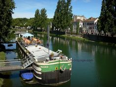 Melun: River Seine, moored barge, restaurant terrace, banks of the River Seine, facades of the city and trees along the water - France-Voyage.com