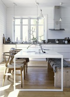 white kitchen with wooden floors and chairs | modern table with vintage chairs…