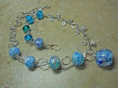 Sterling silver wire and transparent blue & green moretti glass beads with dichroic sparkles necklace by RaptFyre on Etsy