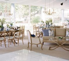 Wedding reception design with lounge areas featuring linen furniture and gold accents,  uncovered wooden reception tables, lace runners, chandeliers and white florals in blue and white chinoiserie. Event design and florals by Lauren Chitwood Events, image by Bella Grace Studios.