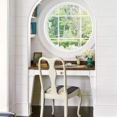 The space beneath a round, porthole-inspired window is closed in to create an office nook. Shelves in the niche around the window are a hiding spot for books, and desk's wood top further enhances the subtle nautical theme.