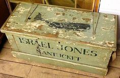 Old sea chest with whale painted on lid.