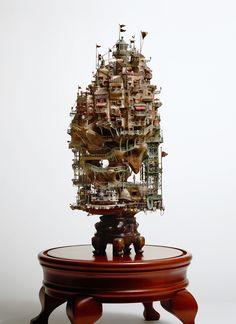 Illustrateur pour le magazine POPYE et ancien architecte, le japonais Takanori Aiba a eu la très bonne idée de mêler ses deux passions pour nous offrir un résultat à coupler le souffle. Semblant tout droit sorti d'un long-métrage du Studio Ghibli, l'artiste originaire de Yokohama mêle bonsaï, papier kraft ou encore plâtre pour littéralement bâtir des mini-villes et palais en taille miniature. Fourmillant de détails et d'ingéniosités où que se pose le regard, féeriques et …