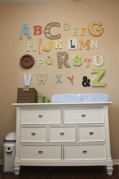 Fun idea!  Have each person responsible for a letter and how to decorate it, then have them bring it to the party to put on baby's wall.