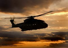 A Royal Air Force Merlin helicopter in flight at sunset.