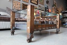 """coffee tables by rogue decor co. - locally reclaimed beams from an old bridge. each was planed, stained and sealed. metal was then inset and sandwiched between the wood and finished off with a wood inset showing the """"before"""" of the wood. 7 antique apothecary drawers are on each side (for a total of 14) in a custom welded frame. woven leather belt blanks create a shelf between the drawers and 1/2"""" tempered glass top. it is completed with antique cast iron double casters."""