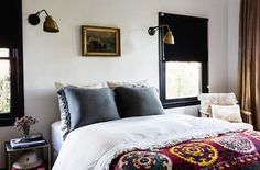 A step up from the air mattress the couple used to have for visitors, the guest bedroom features a vintage suzani blanket and Atelier de Troupe sconces.