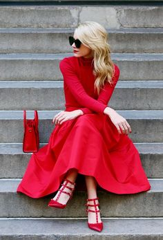 Atlantic-Pacific in a read turtleneck, red skirt, red studded heels, red bag, and black sunglasses