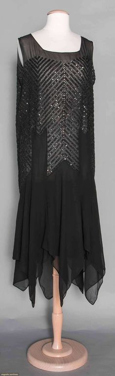"BEADED DANCE DRESS, LATE 1920s  Black silk chiffon, handkerchief hem, rows of black beads & sequins in chevron patterns, sleeveless, B 40"", H 40"", L 50"", (minor sequin & bead losses) excellent. 58"
