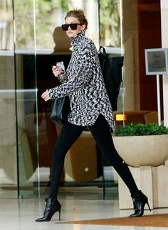 Gigi Hadid wears a sweater, leggings, and ankle boots