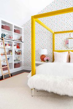 A ladder on rails is fitted against white floor-to-ceiling toy shelves positioned facing a white faux fur bench on lucite legs placed on a red border jute rug in front of a gold velvet canopy bed. Big Girl Bedrooms, Girls Bedroom, Bedroom Decor, Bedroom Ideas, Upstate New York, Deco Kids, Yellow Bedding, Kids Room Design, Mellow Yellow