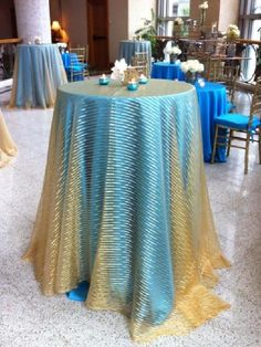 The cocktail table takes on a whole new perspective, when you place a transparent overlay over the bright sea blue. Linens are essential when wanting to make a statement.