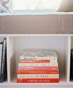 Vintage design books artfully stacked below a ticking-stripe window seat.