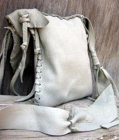 Very soft, and thick elk skin leather in a light grey color that has undertones of sage green. The Elk leather has natural character marks and variation. The bag is unlined, simple, with no pockets. The strap is long (55) and laced in sections. Very comfortable to wear. The bag is small and light at 9 by 7. Made entirely by hand. One of a kind. Natural raw edges. Deer antler bobble.