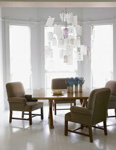 modern dining room with club chairs and a paper chandelier - tips for decorating a small dining room