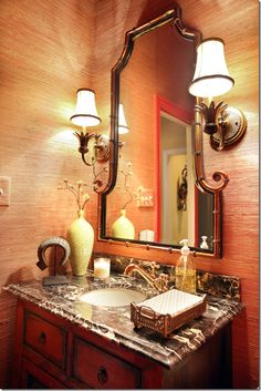 Lovely powder room. Grasscloth wallcovering, red oriental cabinet for vanity, red door casing.