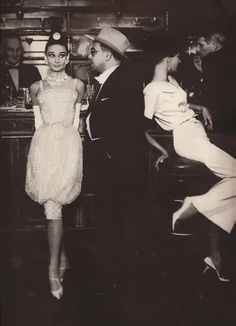 """Harper's Bazaar 1959 - Richard Avedon shoots Audrey and Mel Ferrer for a """"Paris Pursuit""""..the scene: Maxim's on a Friday night: Audrey Hepburn wears Dior's white crystallized puffed tunic silhouette."""