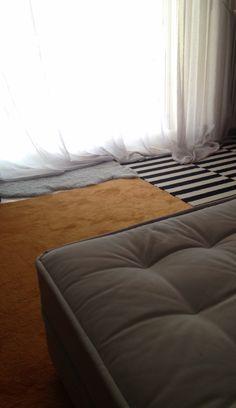 Grey couch + mustard carpet + black & white striped carpet > living roooom