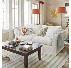 The cottage might be the place for that old tired sofa you love but can't stand looking at - slipcover it in white, add some gentle colour in the accessories and it is fresh and new.  I like the soft aqua here with the unexpected hit of orange in the pillows, lights and drapery trim.   It's not such a bold bright orange that it is jarring, it's  enough add some interest.