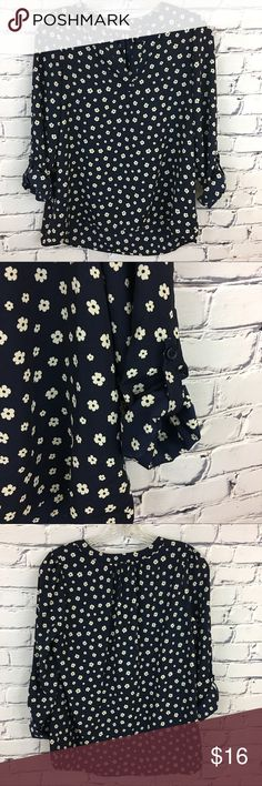 "Navy Blue Daisy Blouse Cute Navy Blue blouse with roll up sleeves and v-neckline. Junior's X-Small.  Back of top is slightly longer than the front.  Excellent condition.  Please see measurements listed below.    🌺Size: Junior's X-Small 🌺Chest: 18"" (flat lay, pit to pit) 🌺Front Length: 22.5""      Back Length: 24.5"" (shoulder to hem) 🌺Material: 100% Polyester Tops Blouses"
